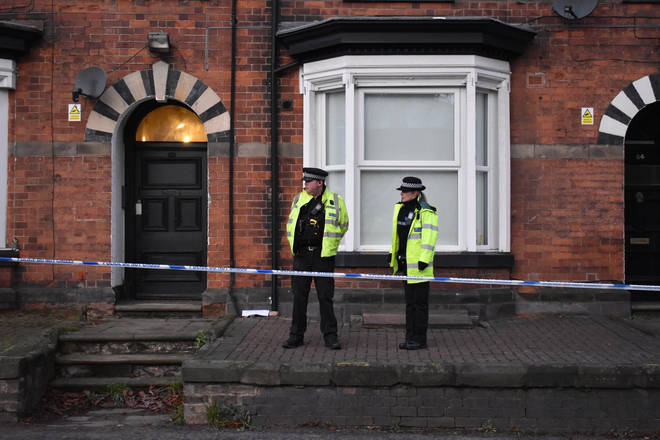 Police officers standing guard outside a three-storey block of flats in Woverhampton Road, Stafford, where a property is being searched.