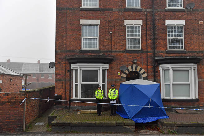 Police officers outside a three-storey block of flats in Stafford as they search a property.