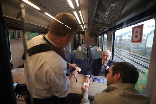 Jeremy Corbyn has his tickets checked on a train