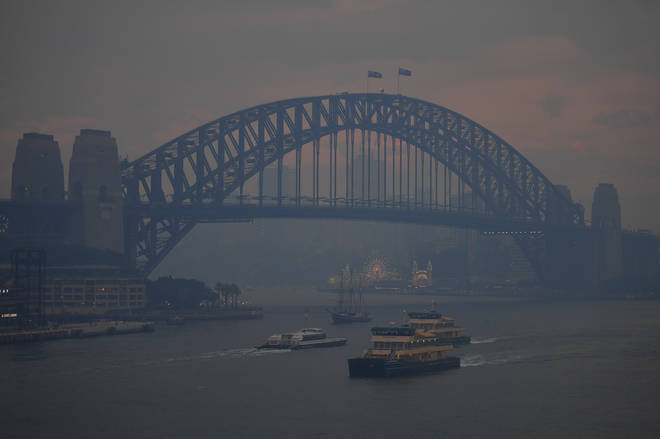 Commuter ferries sail past the Sydney Harbour Bridge as smoke haze from bushfires in New South Wales