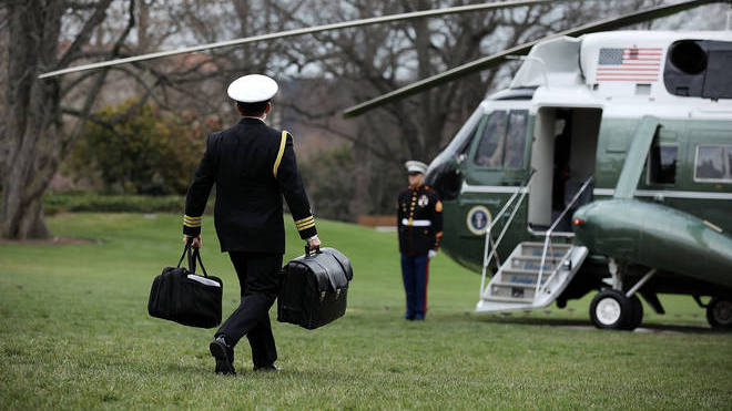 "A White House military aide carries the nuclear ""football"""