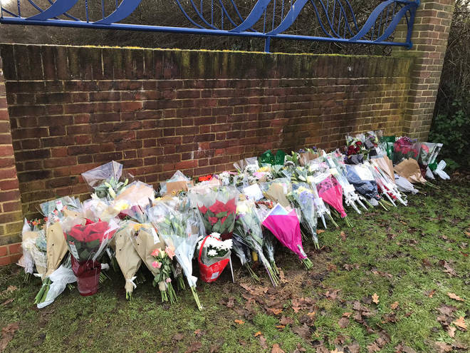 Floral tributes are laid outside Debden Park High School