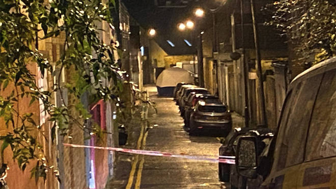 Police remain at the scene of the fatal stabbing in Hackney today