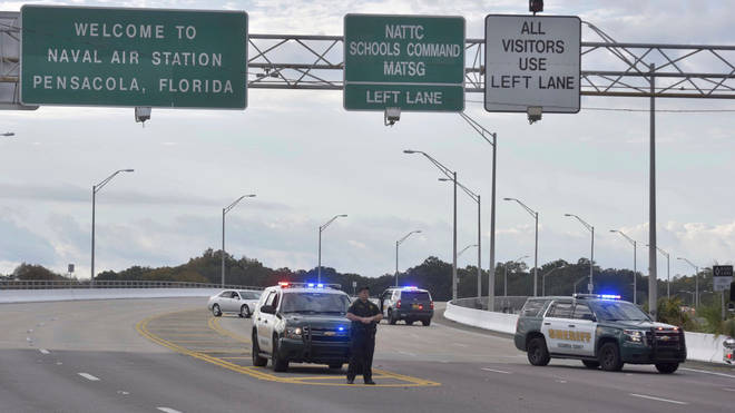 Police vehicles block the entrance to Naval Air Station Pensacola