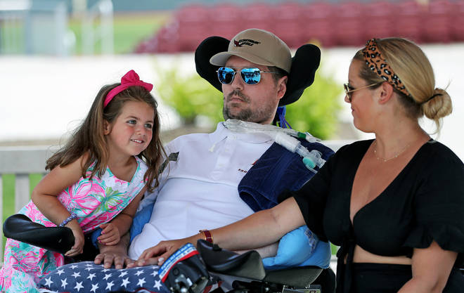 Pete Frates, centre, sits with his four-year-old daughter Lucy and wife Julie at a dedication ceremony at Boston College.
