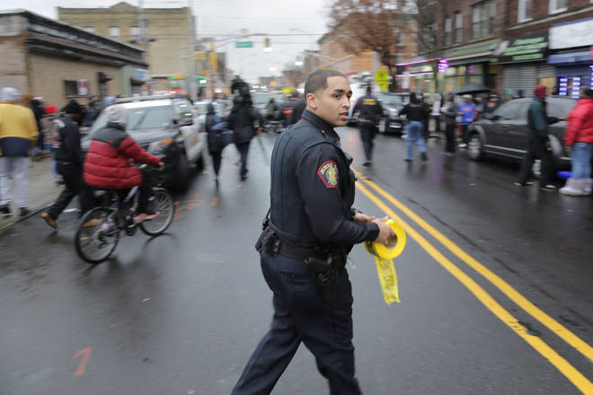 A police officer pushes pedestrians back from the scene of a shooting in Jersey City, N.J.
