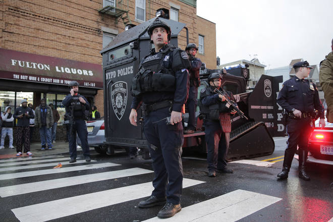 Emergency responders move heavy equipment near the scene of a shooting in Jersey City, N.J.