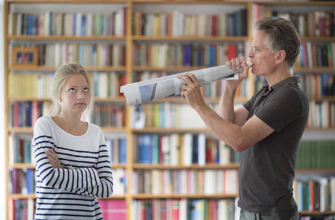 A parent tries to speak to his teenage daughter through a megaphone
