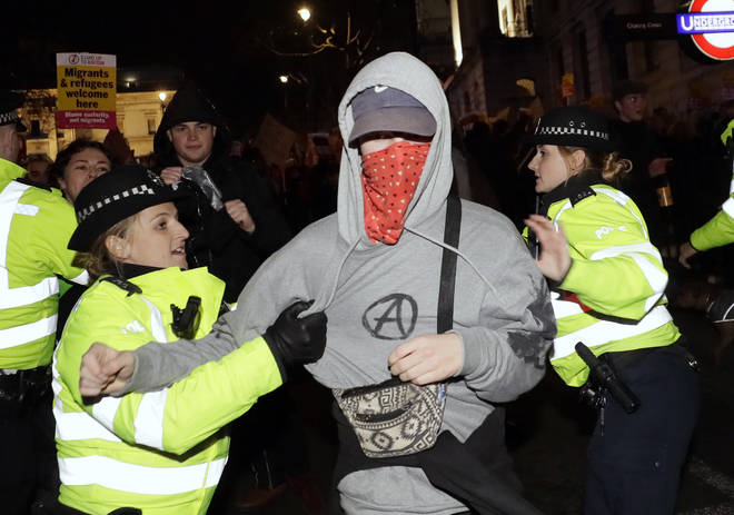 One person with his face covered is accosted by police officers