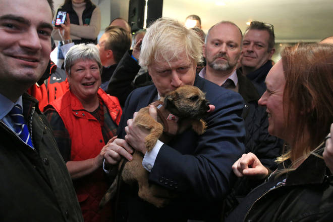 Mr Johnson kisses a dog he is handed at the event