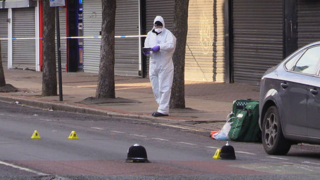 Forensics officers work at the scene