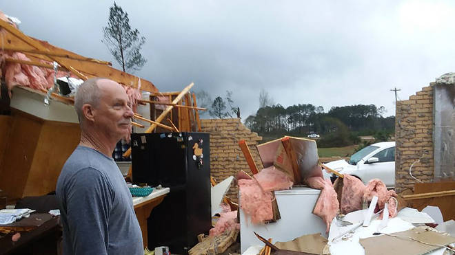 Jason Ford stands in his damaged mobile home on Highway 567, north of Liberty, Miss