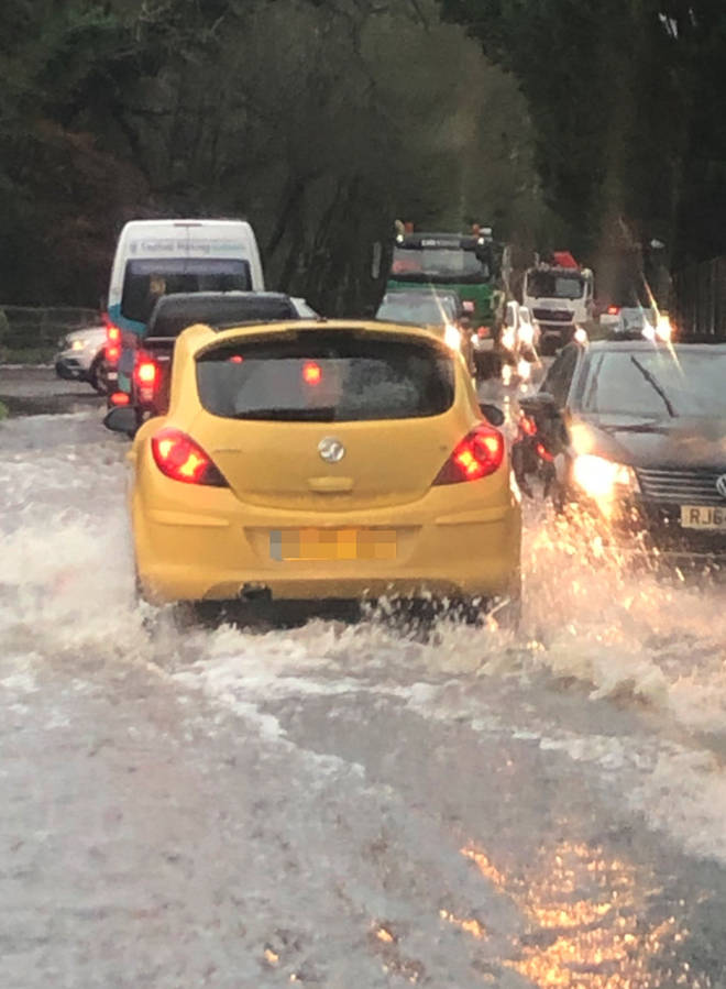 Traffic makes its way through floods near the M23