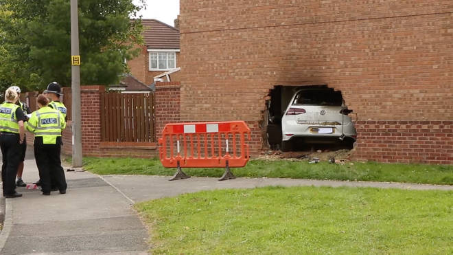 This pictures show the horror crash as a car ploughed through the wall of a house