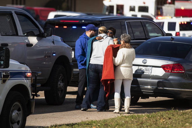 Family and friends comfort each other outside the scene