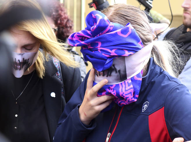 A 19-year-old covers her face after a Cyprus court deemed she lied about being gang raped