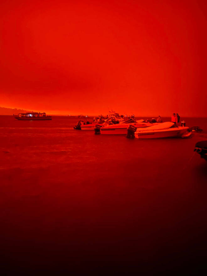 A blood-red sky is seen across the coast as residents flee to boats
