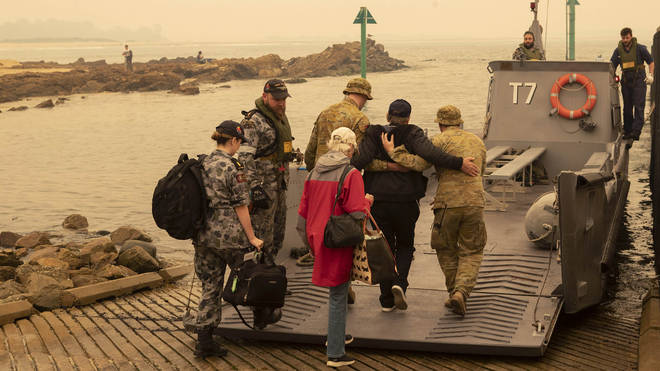 Residents board a landing craft as evacuations take place across coastal regions