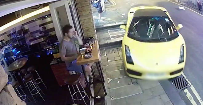 The supercar narrowly avoided a man sitting outside a bar