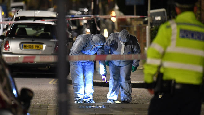 A forensics team examines the murder scene in north London