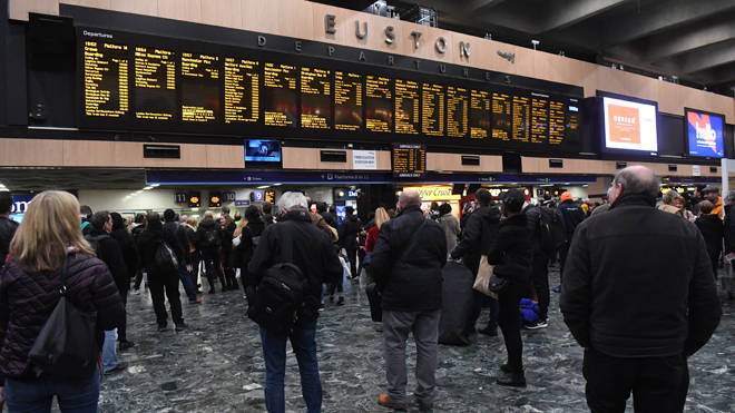 Commuters wait for trains at Euston station in London
