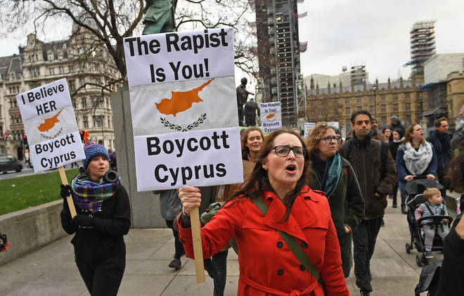 Demonstrators walk past the Houses of Parliament in central London, as they take part in a protest march in support of the British woman convicted in Cyprus of lying about being gang-raped.