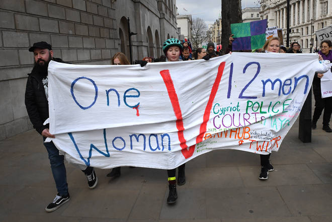 "A banner reads ""One woman versus 12 men""."