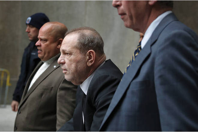 Harvey Weinstein, third from left, leaves court in New York.