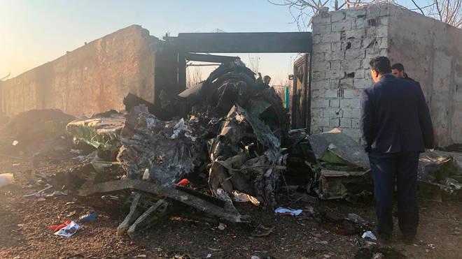 Investigators look at debris following the crash