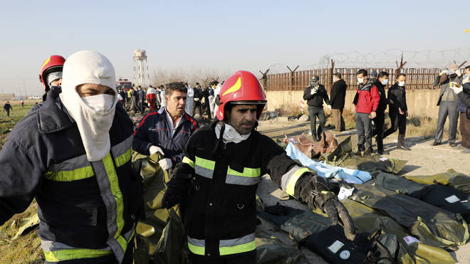 Rescue workers carry bodies away from the crash