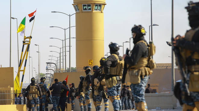 Iraqi soldiers stand guard in front of the US embassy