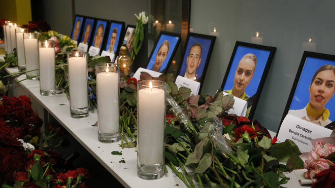 Flowers and candles are placed in front of portraits of the flight crew members of the Ukrainian 737-800 plane that crashed on the outskirts of Tehran