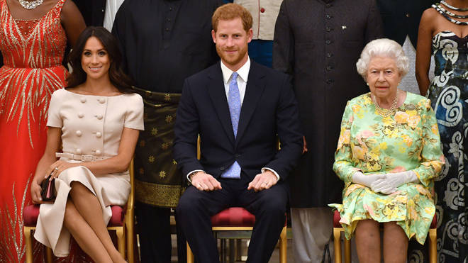 Meghan Markle, Prince Harry and the Queen pictured together in 2018 at the Queen's Young Leaders Awards Ceremony at Buckingham Palace, London