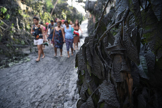 Residents walk along a muddied road after Taal volcano began spewing ash over Tanauan town