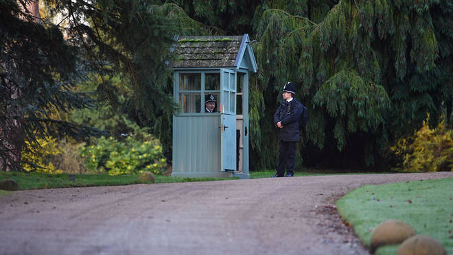 Police stand guard today at the entrance to the Queen's Sandringham estate