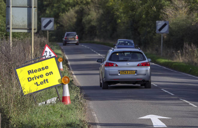 A vehicle with diplomatic plates passes a Please Drive on Left sign and road marking that have been placed on the B4031 outside RAF Croughton, in Northamptonshire, where Harry Dunn, 19, died.