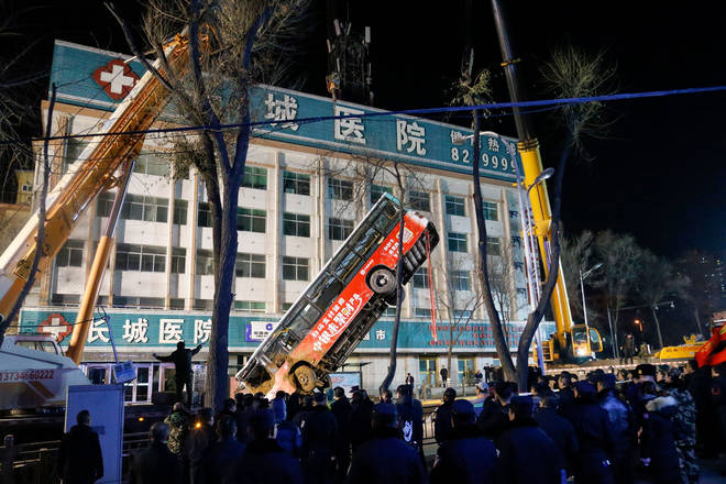 A bus is lifted out after a road collapse in Xining in China's northwestern Qinghai province