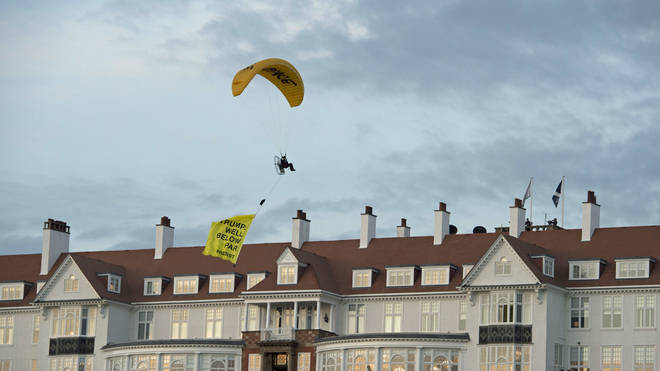 A Greenpeace protester flies within metres of President Trump at his Turnberry resort.