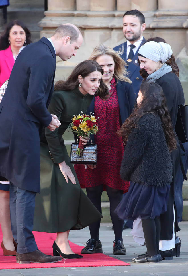 Kate is given a bunch of flowers by a young girl