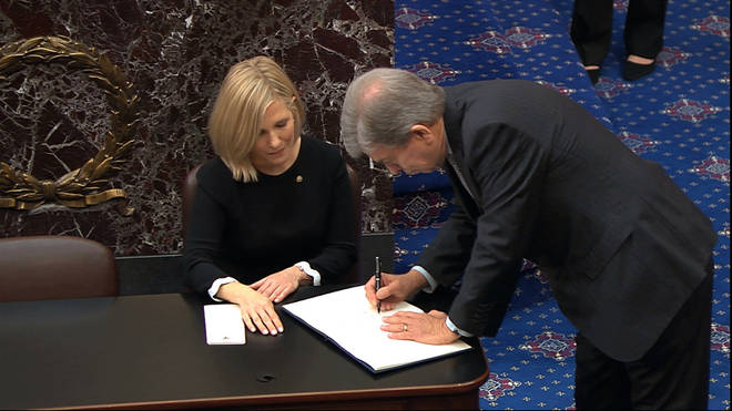 Senators were called up one by one to sign the oath book