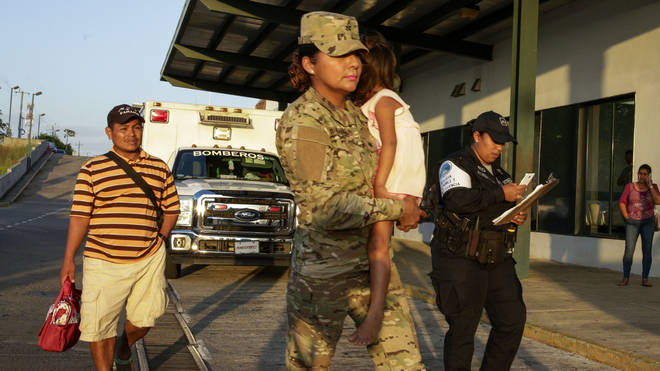 Jose Gonzalez, left, follows his 5-year-old daughter, carried by a police officer, as they leave a hospital in Santiago, Panama,