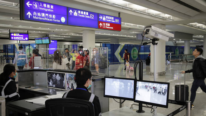 An official uses a temperature scanner to monitor passengers arriving at Hong Kong International airport