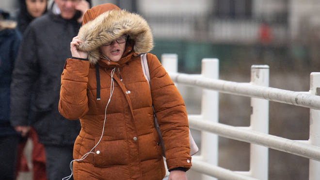 A woman shields herself from biting wind in London as temperatures are set to plummet