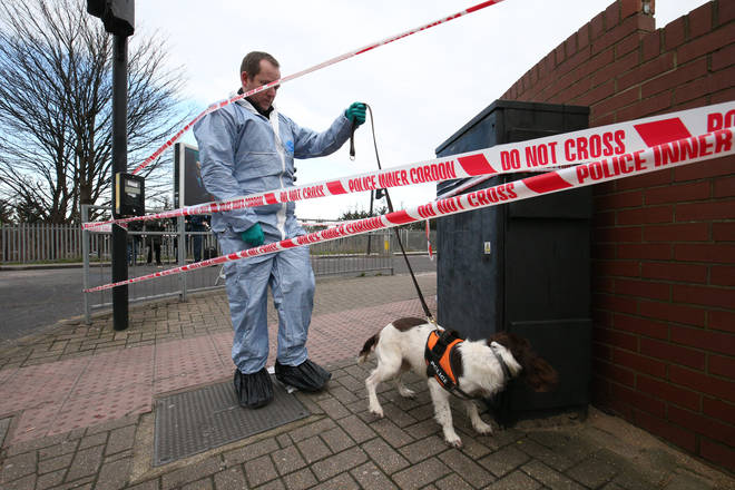 Police with a sniffer dog near the scene in Seven Kings