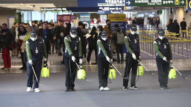 Officials spray anti-bacterial liquid at an airport in China
