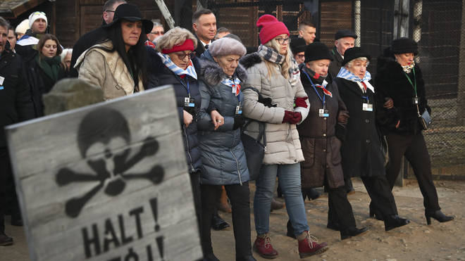 Poland's President Andrzej Duda walks along with survivors through the gates of the Auschwitz Nazi concentration camp in Oswiecim, Poland