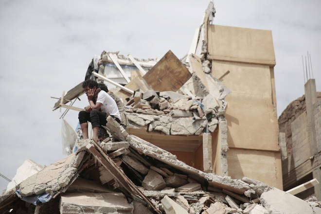 A boy sits on his destroyed house in Yemen