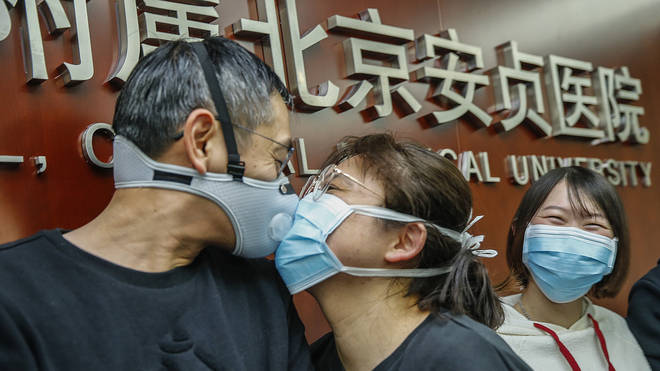 A medical worker being sent to Wuhan kisses goodbye to his partner