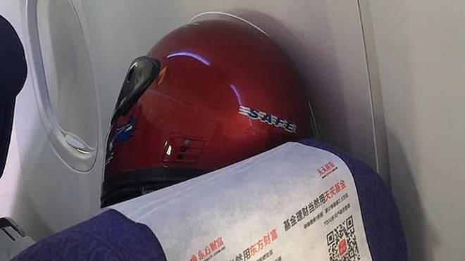 The man was seen on board the nine-hour flight wearing a crash helmet