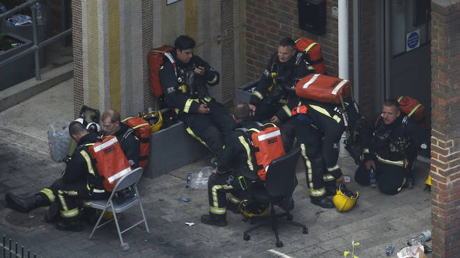 Firefighters rest after going into burning building
